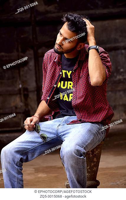Young man with checked shirt looking at camera, Pune, Maharashtra