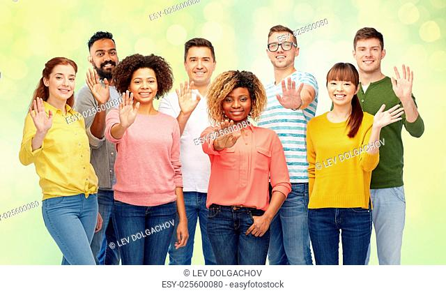 diversity, race, ethnicity and people concept - international group of happy smiling men and women waving hand over summer green lights background