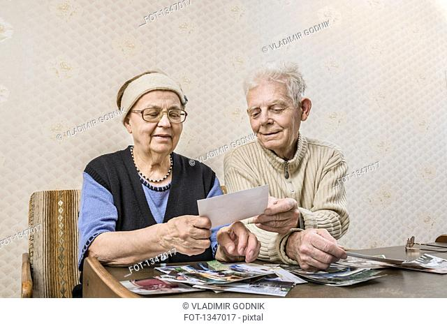 Senior couple going through pictures at home