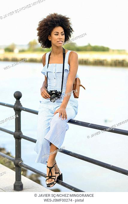 Portrait of fashionable young woman with camera and backpack