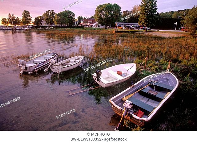 row boats sit in shallow water at sunset in Eagle Harbor, USA, Wisconsin, Door County, Ephraim