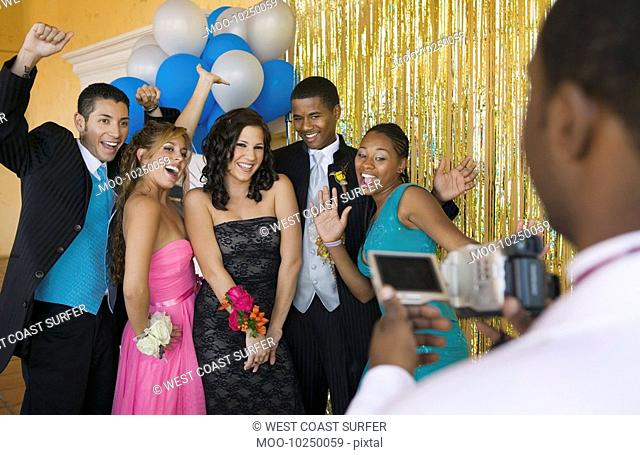 Well-dressed teenagers posing for video camera at school dance
