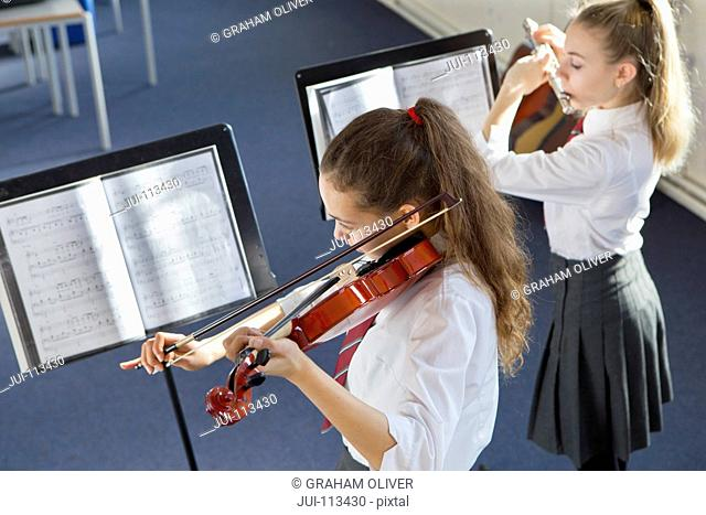 High school students playing violin and flute and sheet music in music class