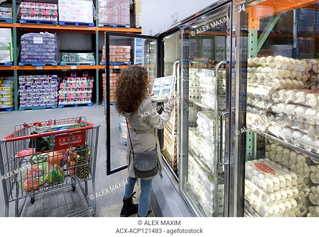Woman picking a crate of omega-3 eggs from a fridge at Costco Wholesale membership warehouse store food section. British Columbia, Canada 2017