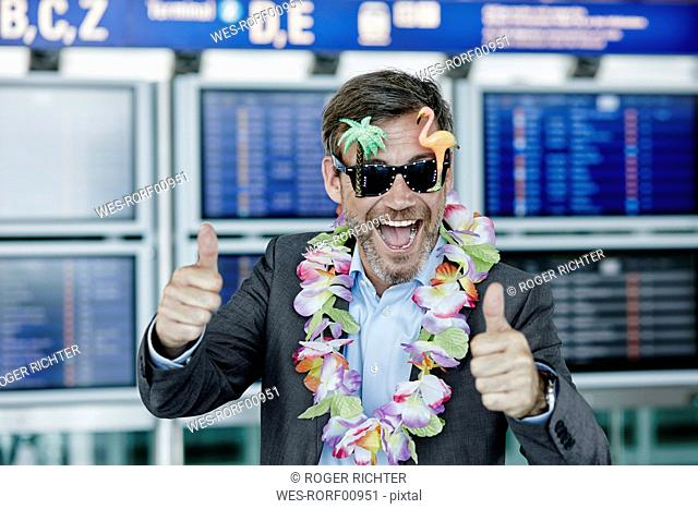 Happy businessman dressed up as tourist at the airport