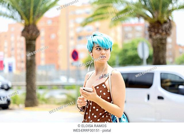 Spain, portrait of young woman with blue dyed hair listening music with earphones and smartphone