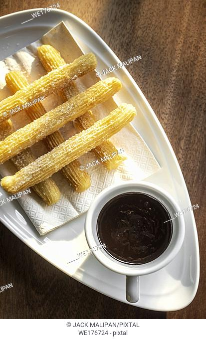 churros con chocolate traditional spanish sweet breakfast set on wooden table