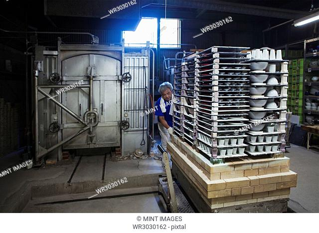 Interior view of Japanese porcelain workshop, man preparing large stack of porcelain objects for kiln