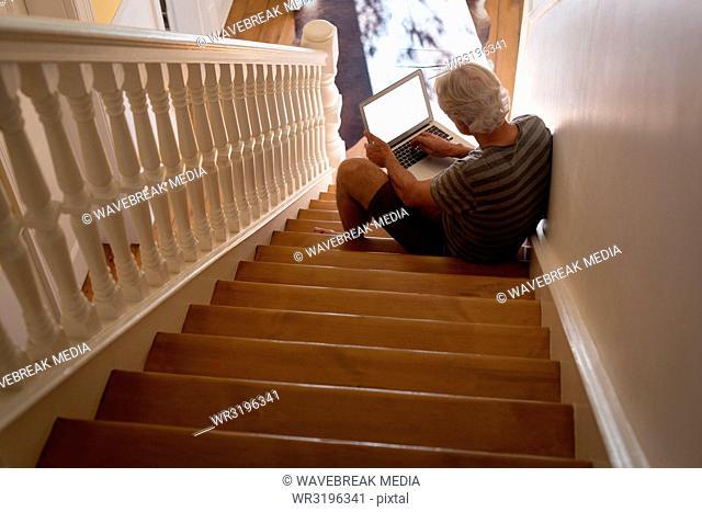 Senior man using laptop on stairs