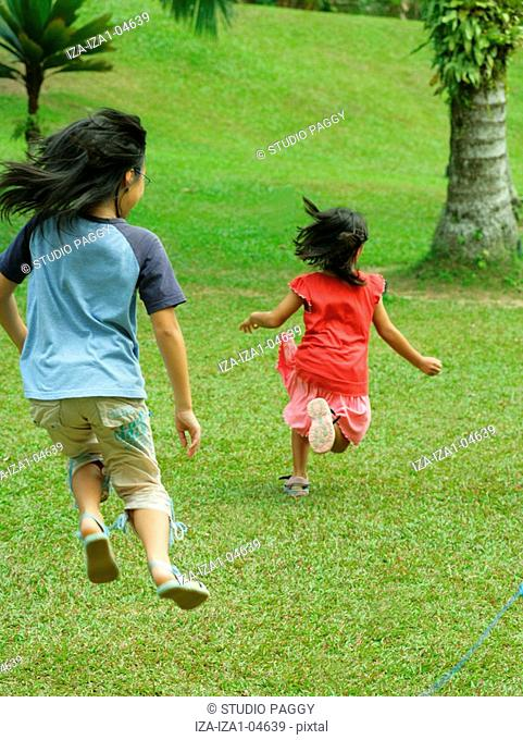 Rear view of a girl chasing her sister in a park