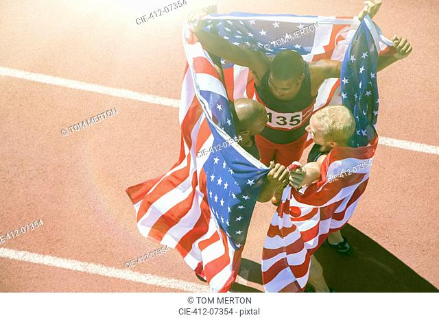 Track and field athletes holding American flags on track