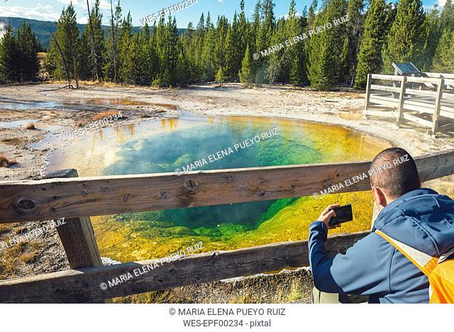 USA, Wyoming, Yellowstone National Park, man taking photos at Morning Glory Pool