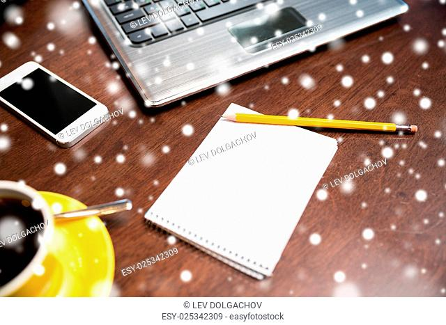 business, education and technology concept - notebook with pencil, laptop, coffee and smartphone on table over snow