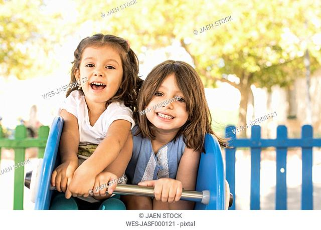 Two little girls playing on a playground