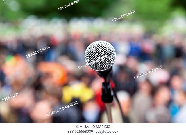 Microphone in focus against blurred crowd. Demonstration