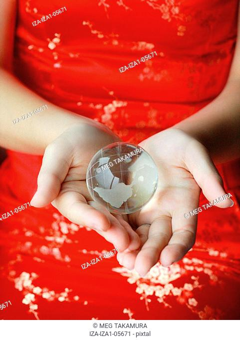 Mid section view of a woman holding a globe