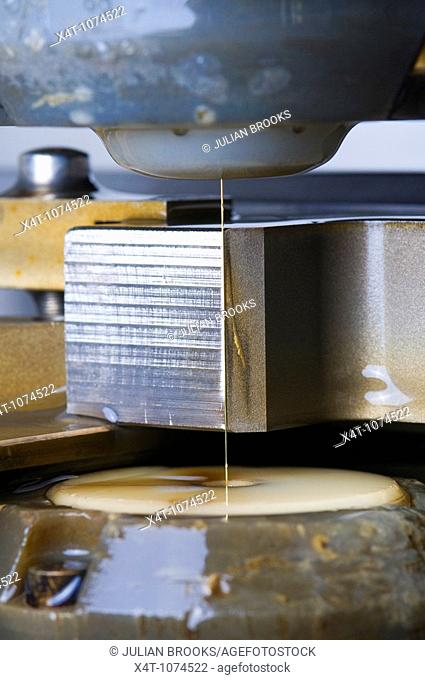 close up of a wire erosion machine shaping a piece of steel, precision engineering  Water cooling system turned off