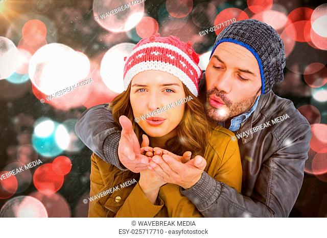 Composite image of happy young couple blowing kiss