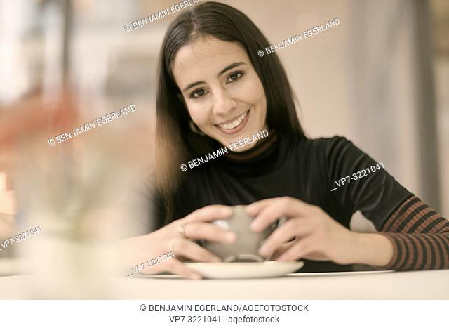 portrait of happy woman holding coffee cup while enjoying break at table in café, in Munich, Germany