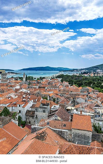 Aerial view of coastal city rooftops under cloudy sky, Trogir, Split, Croatia