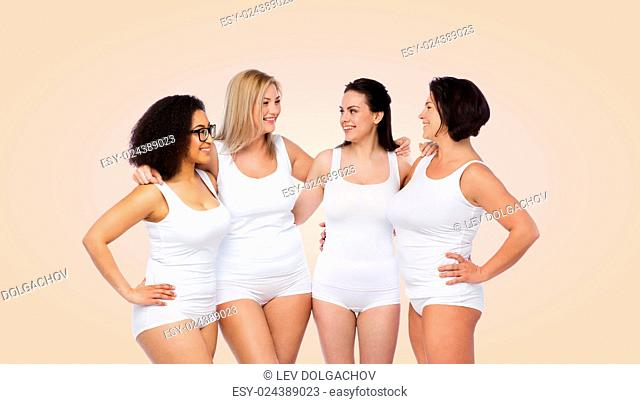friendship, beauty, body positive and people concept - group of happy women different in white underwear over beige background