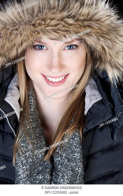 Young woman in a fur trimmed hood and winter coat; Edmonton, Alberta, Canada