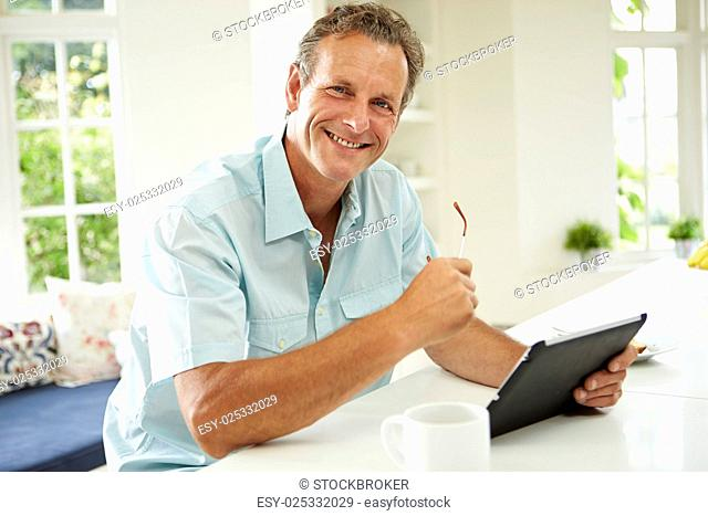 Middle Aged Man Using Digital Tablet Over Breakfast