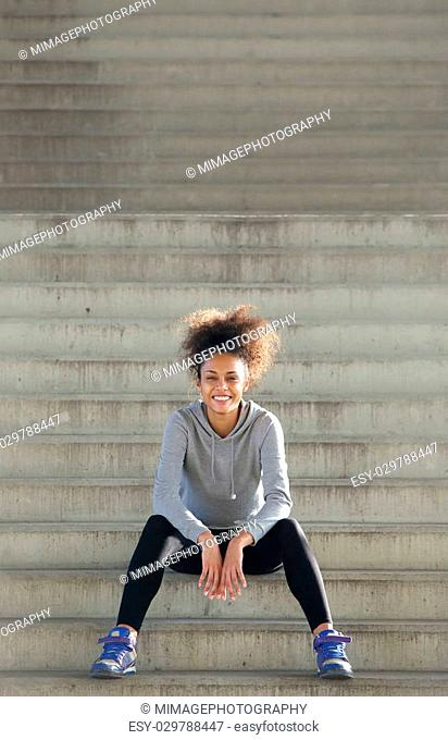 Portrait of a happy young african american sports woman sitting steps outdoors