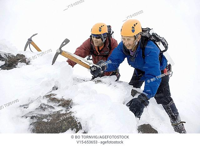 Mountaineers climbing snow covered mountain with crampons and ice axes