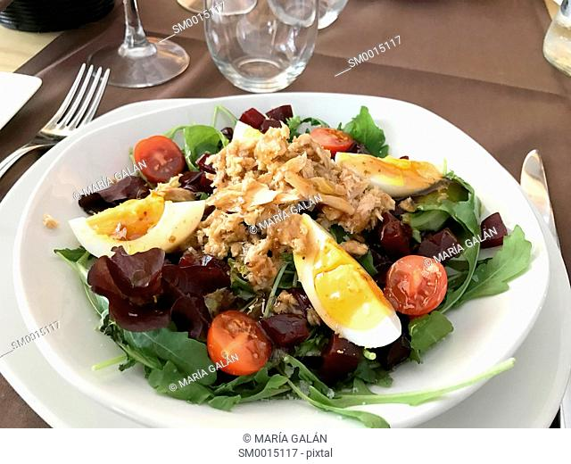 Mixed salad made of lettuce, cherry tomatoes, eggs and tuna with olive oil. Spain