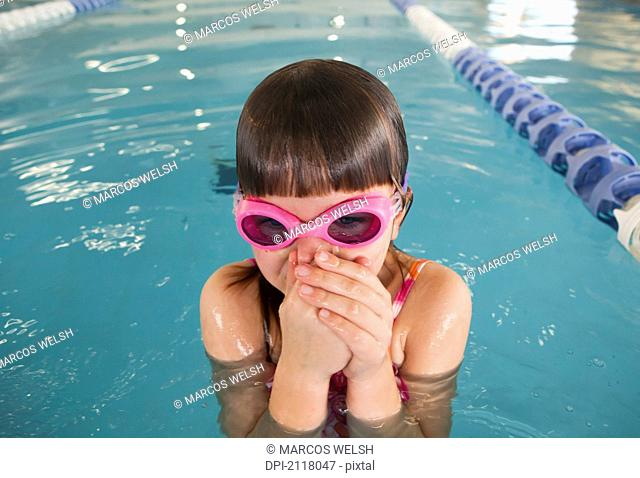 A young girl wearing pink goggles and plugging her nose in a swimming pool, gold coast queensland australia