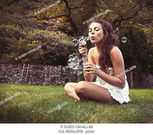 Young woman sitting in field blowing bubbles