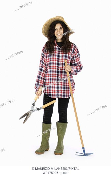 Young farmer with shears and hoe in hands, she is wearing a straw hat, checked shirt and green rubber boots
