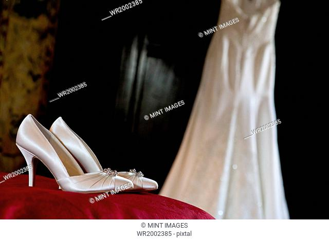 White satin high heeled wedding shoes and a dress hanging up