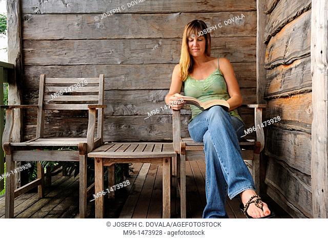 Woman reading at rustic inn, Binna Bura Rain Forest, Australia