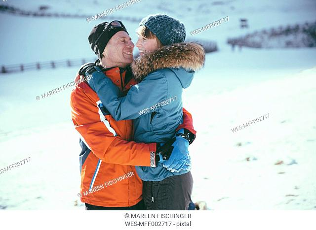 Italy, Val Venosta, Slingia, happy couple hugging in winter landscape
