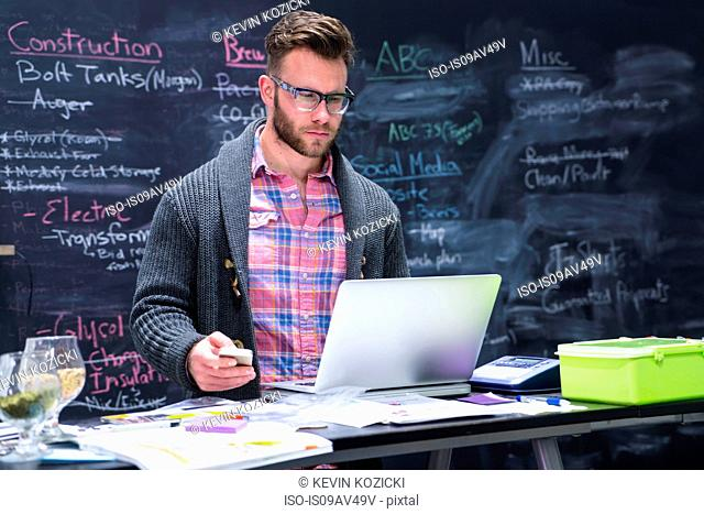 Young man in workplace using laptop holding smartphone