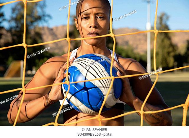 Portrait of woman behind football goat net holding football looking at camera