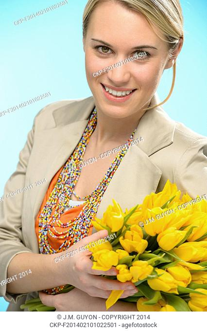 Woman with spring flowers yellow tulips bouquet on blue background
