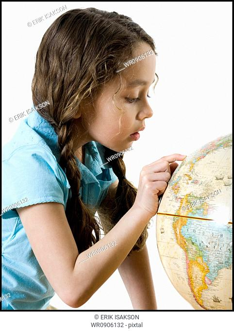 Profile of a girl looking at a globe