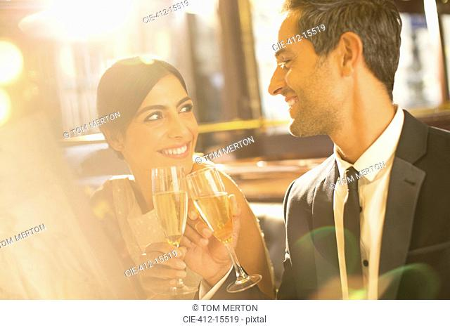 Well-dressed couple toasting champagne flutes in restaurant