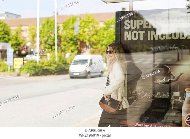 Young woman carrying shoulder bag leaning on poster seen through glass at bus stop