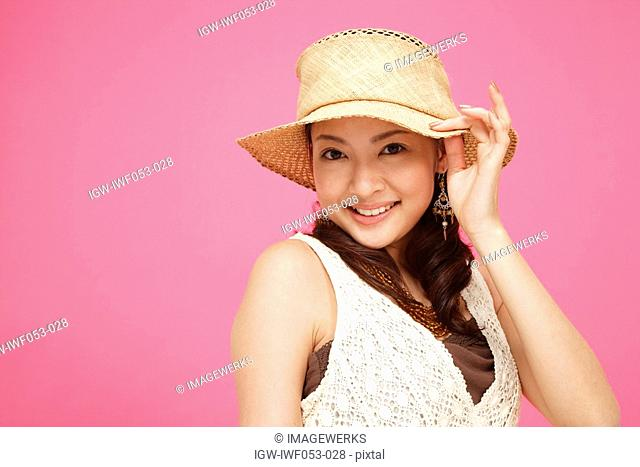 Young woman wearing hat, smiling, portrait