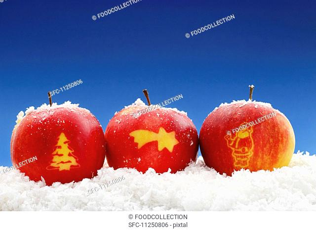 Three apples carved with Christmas symbols