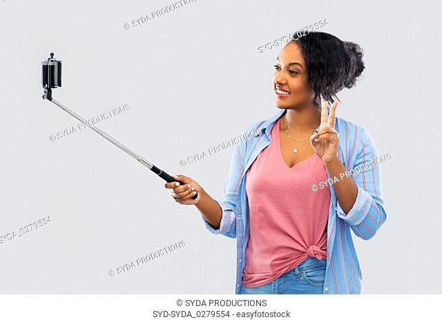 african american woman taking selfie by smartphone