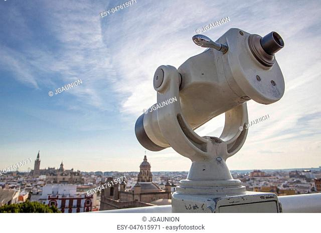 Turistic telescope pointing to old town landmarks over Metropol Parasol roof, one of the best view of the city of Seville, Spain