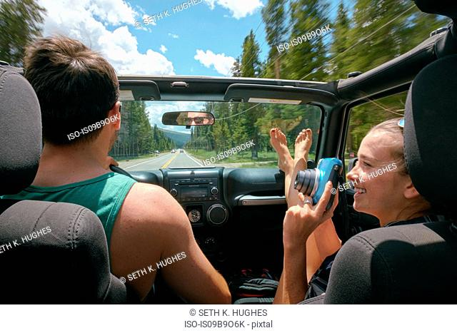Young woman with instant camera driving on road trip with boyfriend, Breckenridge, Colorado, USA