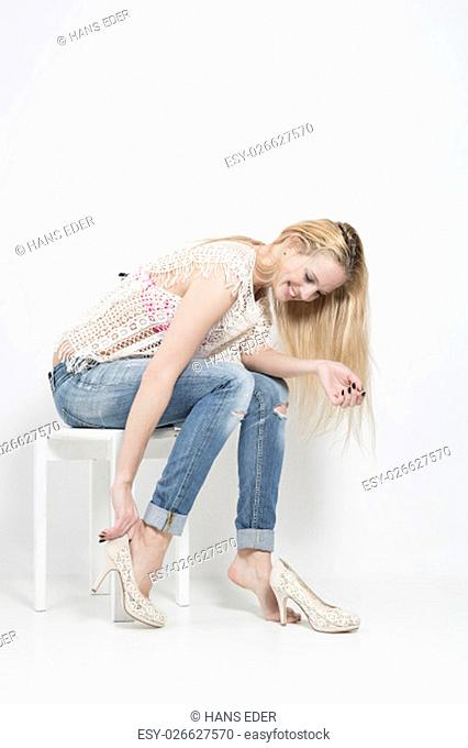 young woman with long blond hair wearing jeans and white crochet tried a pair of shoes
