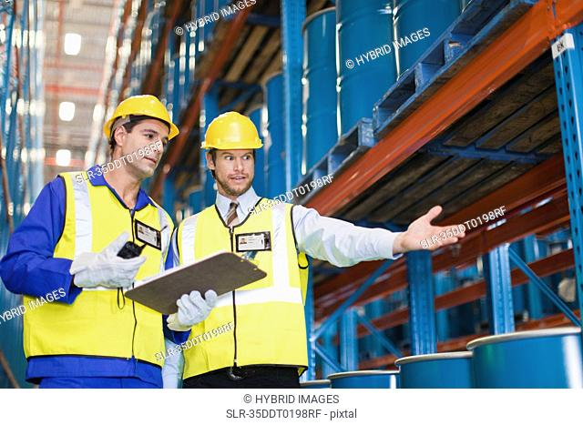Workers with containers in warehouse