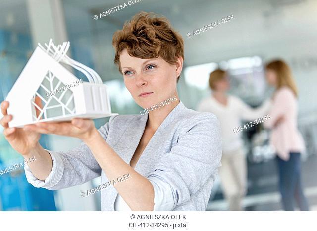 Focused female architect examining model in office